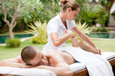 Young masseuse massaging and stretching the body of an attractive man in a tropical hotel garden near a swimming pool. — Stock Photo