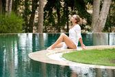 Atraktivní mladá žena sedět na okraji bazénu — Stock fotografie