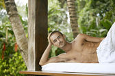Portrait of a young man relaxing on an outdoor spa bed in a tropical garden smiling. — Stock Photo