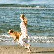 Royalty-Free Stock Photo: Young teenage girl running with her golden retriever along the beach shore.