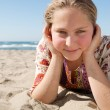 Portrait of a blond girl laying down on a golden sand beach, smiling. — Стоковая фотография