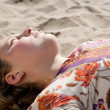 Close up of a young girl laying down on a golden sand beach, relaxing. — Stock Photo