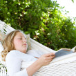 Young teenage girl reading a book while laying down on a hammock in a garden. — Stok fotoğraf