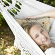 Girl laying down on a hammock in the garden — ストック写真