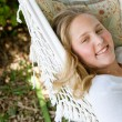 Close up portrait of a young teenage girl laying down on a hammock in a garden — Stock Photo