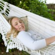 Portrait of a young teenage girl laying down and relaxing on a hammock in a garden — Stok fotoğraf