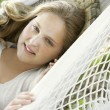 Portrait of a girl laying down on a hammock in the garden, smiling. — Stock Photo