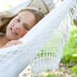 Royalty-Free Stock Photo: Young teenage girl laying down on a hammock in a garden