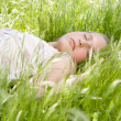 Close up of a beautiful young blond girl sleeping on long green grass in a garden. — Stock Photo #21122143