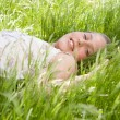 Young teenager laying down on a long green grass garden, smiling at the camera. — Stock Photo