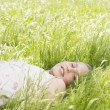 Portrait of girl laying down on long green grass, smiling. — Stock Photo