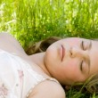 Close up portrait of a beautiful young blond girl sleeping on long green grass in a garden. — Stock Photo