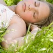 Close up of a beautiful young blond girl sleeping on long green grass in a garden. — Stock Photo