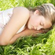 Portrait of a girl sleeping on long green grass in the garden. — Stock Photo