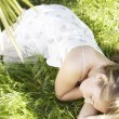 Portrait of a girl sleeping on long green grass in the garden. — Stock Photo #21122299
