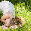 Young teenage girl sleeping while laying down on long green grass in a garden during the summer. — Photo
