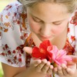 Girl smelling hibiscus flowers while sitting on a green grass garden. — Stock Photo #21122403