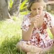 Girl sitting down on green grass, smelling a daisy flower. — Stock Photo #21122449
