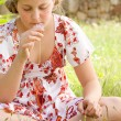 Girl smelling daisy flower while sitting on a green grass garden, close up. — Foto de Stock