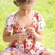 Young teenager pulling petals off a daisy flower, playing at love me love me not. - Foto Stock