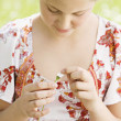 Close up of a girl pulling petals off a daisy flower while sitting on a green field. - Foto de Stock  