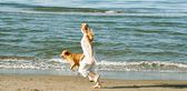 Young teenage girl running with her golden retriever along the beach shore. — Stock Photo