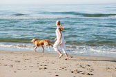 Teenage girl running along a beach shore with her golden retriever during the early morning. — Stock Photo