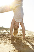 Girl doing cartwheels on the beach with the sun filtering through her legs. — Stock Photo