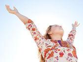 年轻的女孩对蓝色天空提出她双臂呼吸新鲜空气. — 图库照片