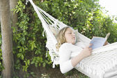 Girl laying down on a hammock in the garden, reading a book. — Stock Photo