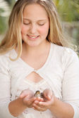 Teenage girl holding a baby bird in her hands while sitting at a home garden — Stock Photo