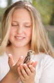 Close up portrait of a young teenage girl holding a baby bird in her hands, smiling. — Stock Photo