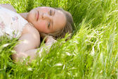 Young teenager laying down on a long green grass garden, looking at the camera. — Stock Photo