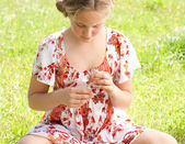 Young teenager pulling petals off a daisy flower, playing at love me love me not. — Stock Photo