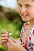 Young teenager pulling petals off a daisy flower — Stock Photo