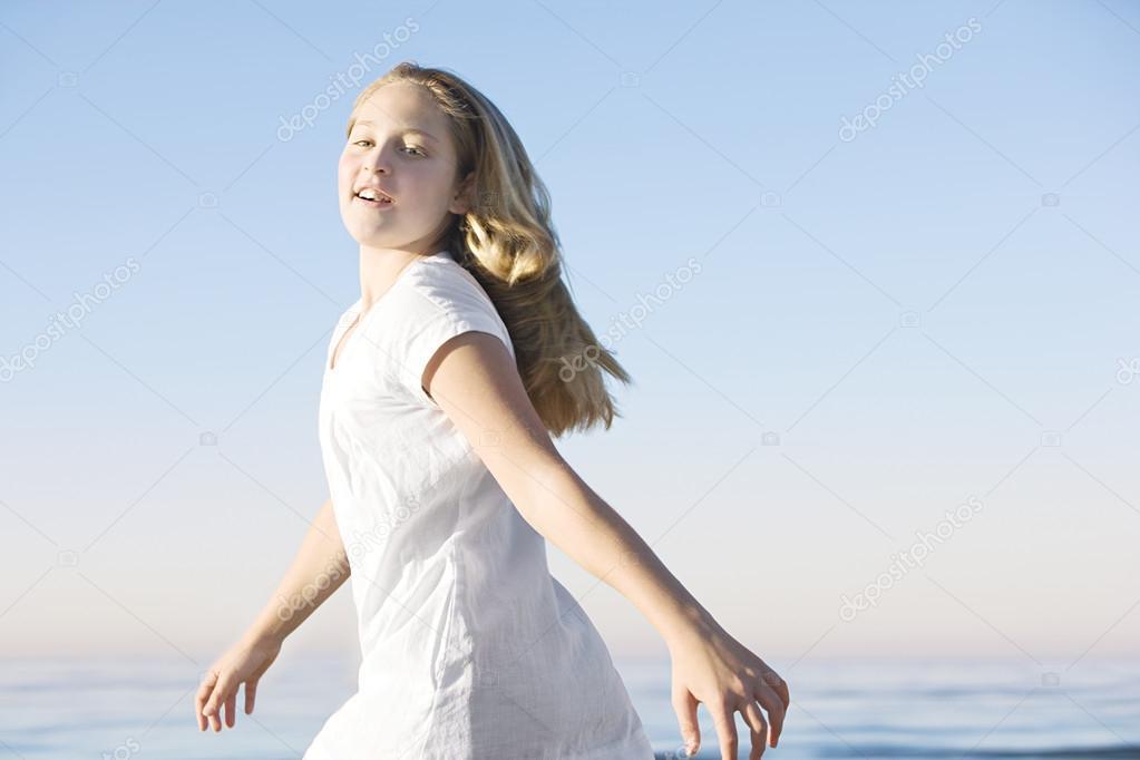 在背景中的蓝色天空和地平线与沙滩散步的女孩