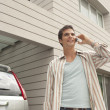Stock Photo: Young businessmusing cell phone at home, standing by his car.