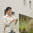 Stock Photo: Young businessmusing smart cell phone near modern building.