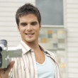 Man using a digital video camera outside his house. — Stock Photo