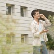 Young man talking on a cell phone, standing by a modern office building. — Stock Photo
