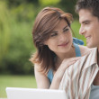 Couple looking at each other while using a laptop computer in home garden — Stock Photo #21183279