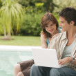 Couple using a laptop by swimming pool, hotel exterior. — 图库照片