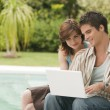 Couple using a laptop at home by swimming pool, exterior. — Stok fotoğraf