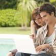 Couple using a laptop by swimming pool, hotel exterior. — Foto de Stock