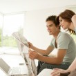 Young couple sharing a newspaper at home while sitting on the sofa. — Stock Photo #21183411
