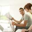 Young couple sharing a newspaper at home while sitting on the sofa. — Stock Photo