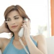 Woman making a phone call at home while sitting on a white sofa. — Stock Photo