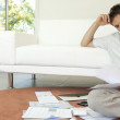 Young man working on his finances, sitting on the floor by the sofa. — Stock Photo