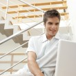 Young professional using a laptop while sitting in a modern stairwell. — Stock Photo