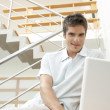 Young professional using a laptop while sitting in a modern stairwell. — Stock Photo #21183869